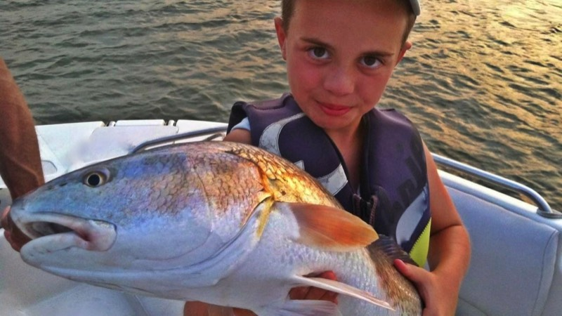 child angler holds up red fish caught on Hilton Head fishing charter